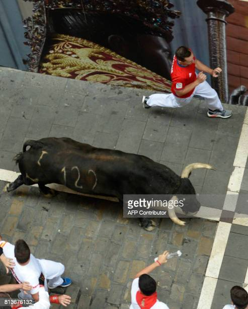 Participants run ahead of a Nunez del Cuvillo's fighting bull during the seventh bull run of the San Fermin festival in Pamplona northern Spain on...