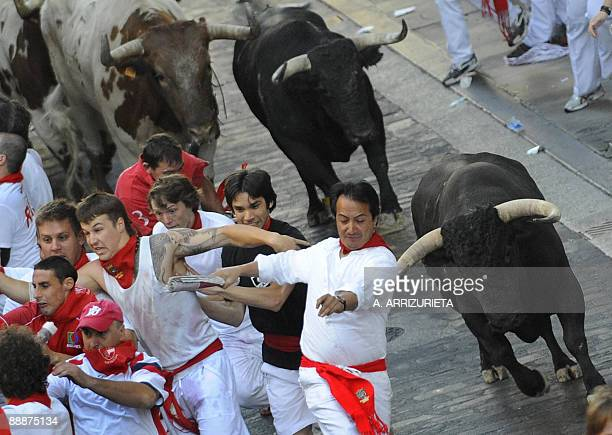 Participants run ahead of Alcurrucen fighting bulls on the second day of the San Fermin festival on July 7 in Pamplona northern Spain On each day of...