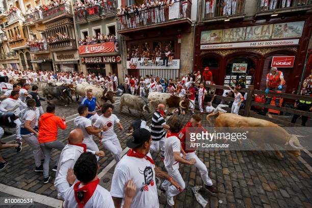 CORRECTION Participants run ahead of Cebada Gago's fighting bulls on the first day of the San Fermin bull run festival in Pamplona northern Spain on...