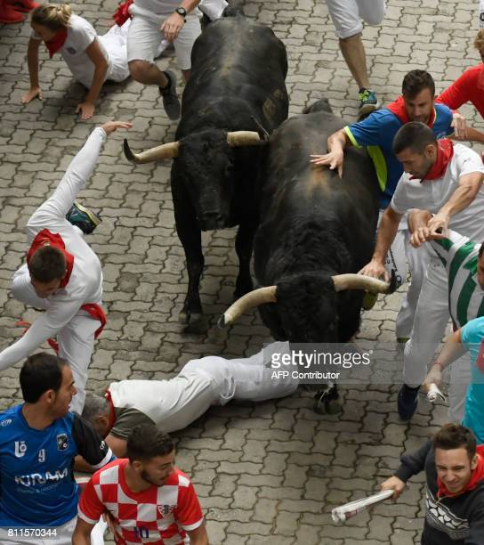 Participants run ahead of Fuente Ymbro's fighting bulls during the fourth bull run of the San Fermin festival in Pamplona northern Spain on July 10...