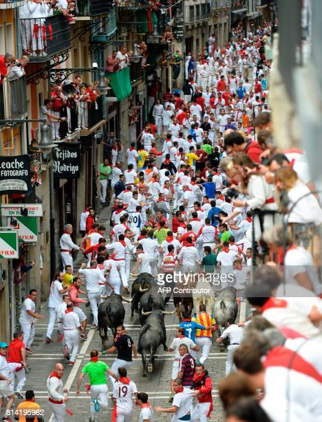 Participants run ahead of Miura's fighting bulls during the eighth and last bull run of the San Fermin festival in Pamplona northern Spain on July 14...