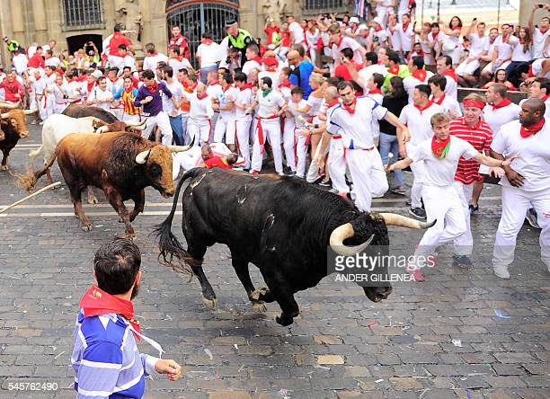 Participants run ahead of Pedraza de Yeltes' fighting bulls on the fourth day of the San Fermin bull run festival in Pamplona northern Spain on July...