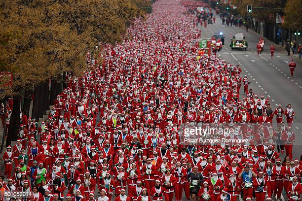 Participants run along Castellana Street during the fourth edition of the yearly Santa Claus 'Papa Noel' race on December 12 2015 in Madrid Spain...