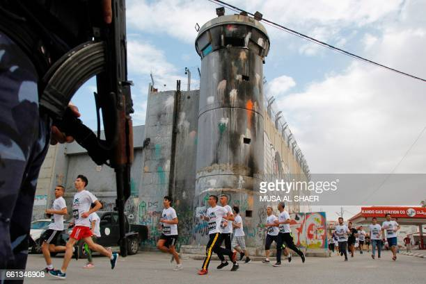Participants run along Israel's controversial separation barrier which divides the West Bank from Jerusalem in the biblical West Bank town of...