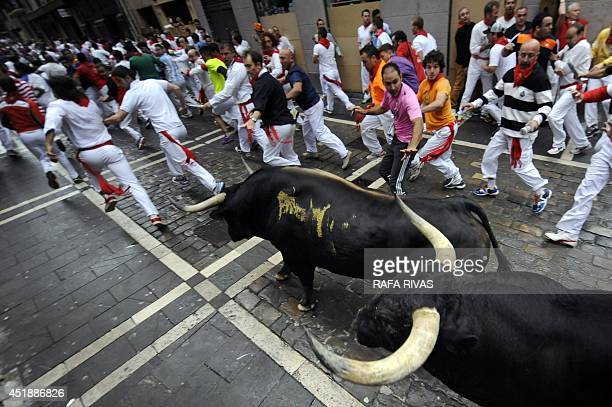 Participants run away from Victoriano del Rio Cortes' bulls during the third bullrun of the San Fermin Festival in Pamplona northern Spain on July 9...