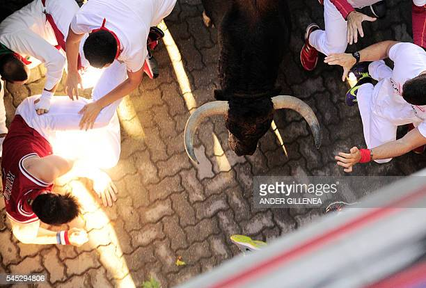 Participants run beside Fuente Ymbro fighting bulls on the first day of the San Fermin bull run on July 7 in Pamplona northern Spain On each day of...