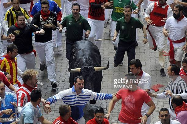 Participants run in front of a Fuente Ymbro bull during the sixth bullrun of the San Fermin Festival in Pamplona northern Spain on July 12 2014 The...