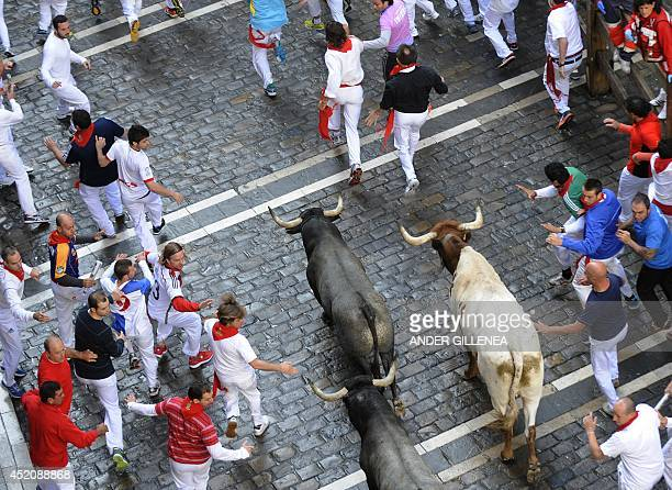 Participants run in front of Adolfo Martin's bulls during the seventh bullrun of the San Fermin Festival in Pamplona northern Spain on July 13 2014...