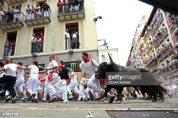 Participants run in front of Del Tajo la Reina's bulls during the second 'encierro' of the San Fermin Festival in Pamplona northern Spain on July 8...
