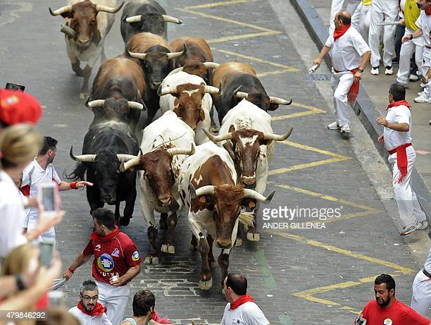 Participants run in front of Del TajoLa Reina's bulls during the second 'encierro' of the San Fermin Festival in Pamplona northern Spain on July 8...