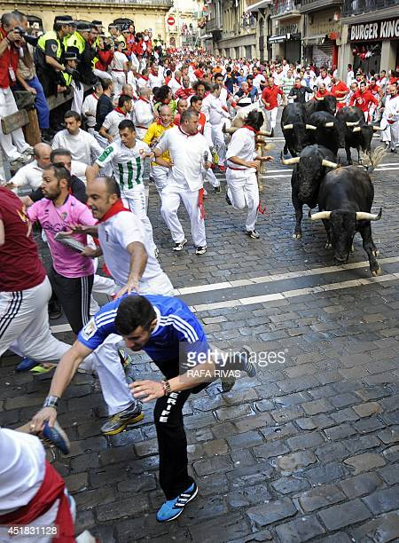 Participants run in front of Dolores Aguirre Ybarra's bulls during the second bullrun of the San Fermin Festival in Pamplona northern Spain on July 8...