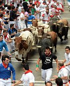 Participants run in front of fighting bulls during the second bullrun of the annual San Fermin Festival in Pamplona Spain on July 08 2015
