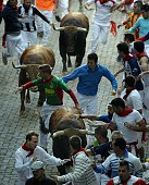 Participants run in front of Fuente Ymbro's bulls during the fourth 'encierro' of the San Fermin Festival in Pamplona northern Spain on July 10 2015...