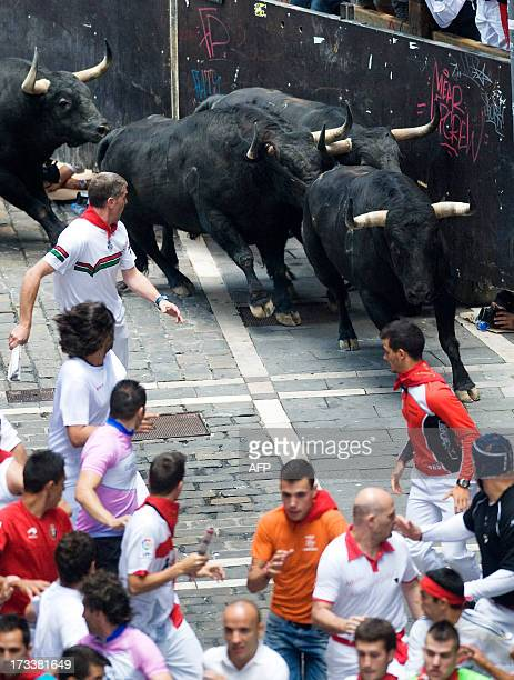 Participants run in front of Fuente Ymbro's bulls during the seventh bull run of the San Fermin Festival in Pamplona northern Spain on July 13 2013...