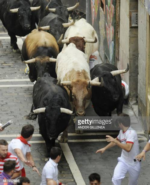 Participants run in front of Garcigrande's bulls during the fourth bullrun of the San Fermin Festival in Pamplona northern Spain on July 10 2014 The...