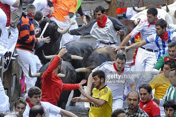 Participants run in front of Jandilla's bulls during the fifth bullrun of the San Fermin Festival in Pamplona northern Spain on July 11 2014 The...