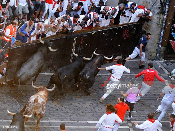 Participants run in front of Miura's bulls during the last bull run of the San Fermin Festival in Pamplona northern Spain on July 14 2013 AFP PHOTO/...
