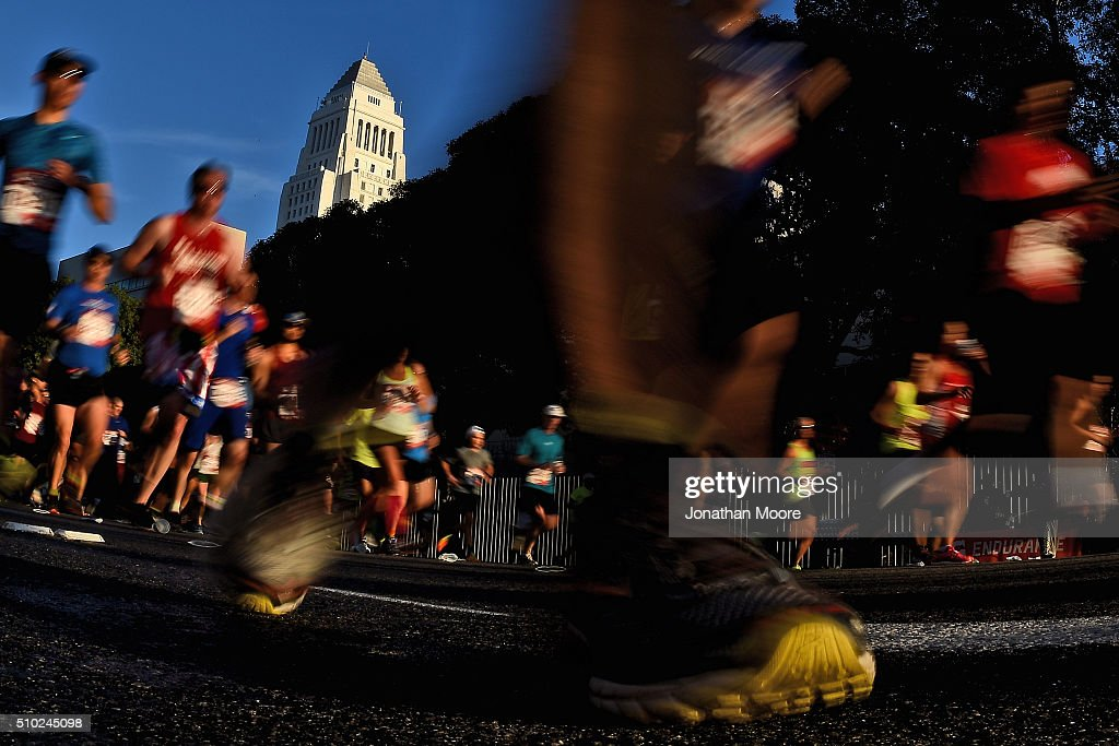 Participants run near Los Angeles City Hall during the 2016 Skechers Performance Los Angeles Marathon on February 14 2016 in Los Angeles California