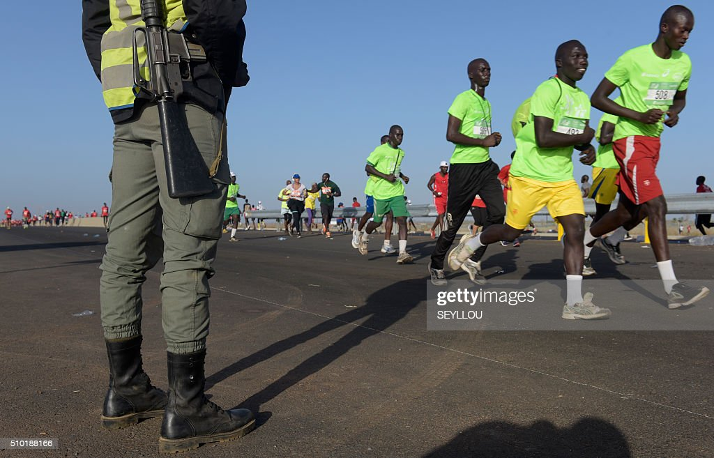 Participants runs next to a gendarme in Dakar on February 14, 2016 during the first ever Dakar International Marathon long 42,195km in 2h 16mm 37s according to official results. The competition organised by the BTP Eiffage society started on February 13 in front of International Conference Center Abou Diouf (Cicad) on the outskirts of Dakar with different runs of 10 km and will end the day after, February 14, with a marathon. The BTP Eiffage society hosted the event to celebrates its 90 years of presence in Senegal. / AFP / SEYLLOU