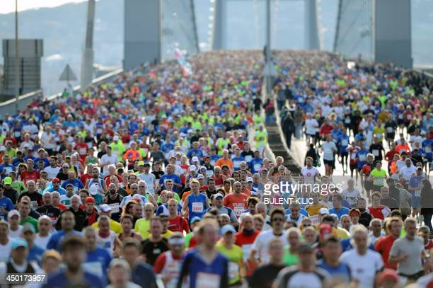 Participants run over the Bosphorus Bridge which links the Asian side to the European side of the city during the 35th annual Eurasia Marathon in...