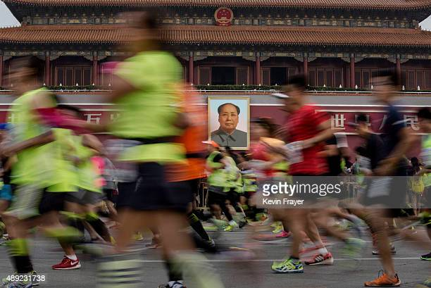 Participants run passed the portrait of the late leader Mao Zedong over Tiananmen Gate while competing in the 2015 Beijing Marathon on a hazy day...