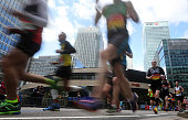 Participants run through Canary Wharf during the 2016 Virgin Money London Marathon on April 24 2016 in London England