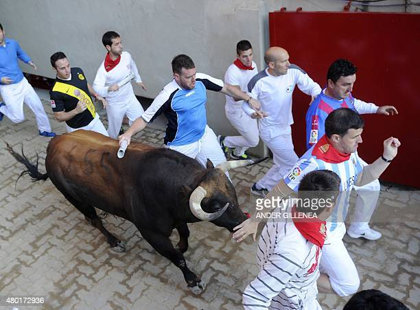 Participants run with Fuente Ymbro's bulls as they arrive at the bullring during the fourth 'encierro' of the San Fermin Festival in Pamplona...