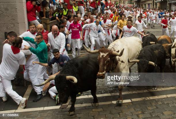 Participants run with Fuente Ymbro's fighting bulls at Estafeta curve during the fourth bull run of the San Fermin festival in Pamplona northern...