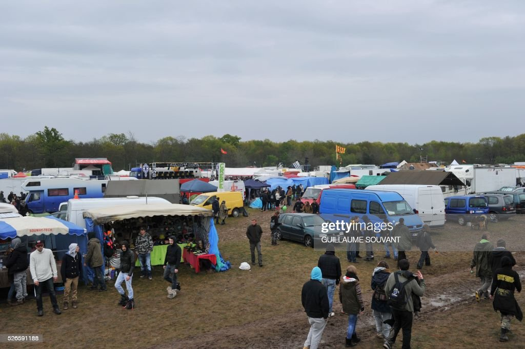 Participants set up their tents as people arrive to the 'Frenchtek 23' Teknival music festival near Salbris, central France on April 30, 2016. / AFP / GUILLAUME