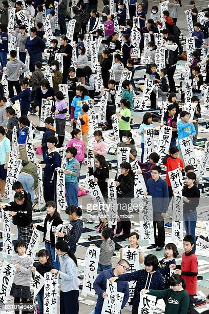 Participants show off their 'Kakizome' the first calligraphy writing of the new year during the annual new year's calligraphy contest at the Fukuoka...