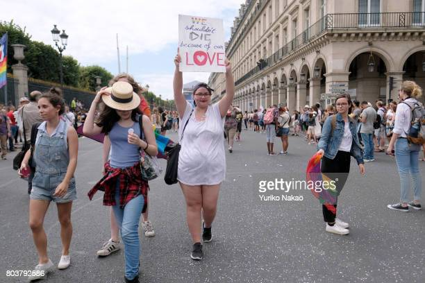 A participants shows a sign reading 'We Exist We are Humans' during the Paris Gay Pride Parade or known as Marche des Fiertés LGBT in France on June...