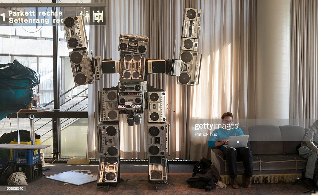 A participants sits with his laptop next to a robot statue built by old ghettoblaster radios at the 31st annual Chaos Communication Congress on December 28, 2014 in Hamburg, Germany. The annual congress is organized by the Chaos Computer Club, Europe's biggest association of computer hackers that has its own code of ethics and in its annual congress seeks to address issues related to society, surveillance, privacy, freedom of information and security.