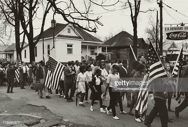 Participants some carrying American flags marching in the Civil Tights march from Selma to Montgomery Alabama USA in 1965 Photographer Peter Pettus