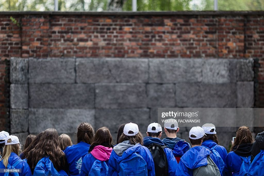 Participants stand in front of the Death Wall as they take part in the annual 'March of the Living' at the former Nazi death camp in Oswiecim (Auschwitz), Poland, on May 5, 2016. Thousands of young Jews from 40 nations marched alongside a handful of Holocaust survivors and Polish teenagers in homage to the victims of the former Auschwitz-Birkenau WWII death camp in southern Poland. / AFP / WOJTEK