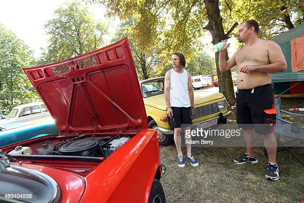 Participants stand in the shade to avoid the heat next to a Lada 1200 automobile at a Trabant enthusiasts' weekend on August 8 2015 near Nossen...