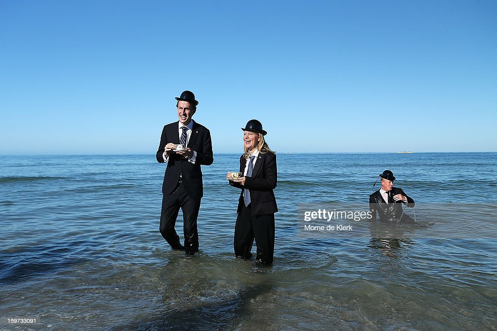 Participants stand in the water in suits and bower hats as part of an art installation created by surrealist artist Andrew Baines on January 20, 2013 in Adelaide, Australia.