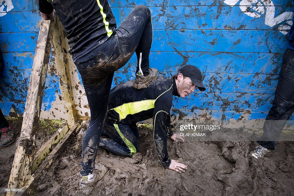 Participants tackle an obstacle in the annual Masters Obstacle Mud Run in Vijfhuizen, Netherlands, on March 16, 2013. Thousands of sporty runners braved the mud trail with difficult obstacles constructed by Dutch Marines. netherlands out