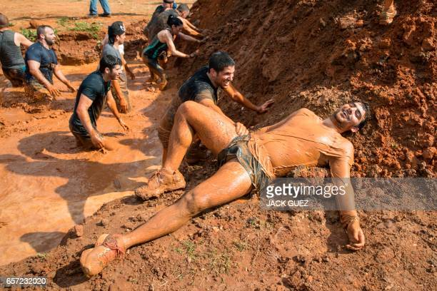 Participants take part in the Mud Day race a 13km obstacle course on March 24 2017 in the Israeli Mediterranean coastal city of Tel Aviv / AFP PHOTO...