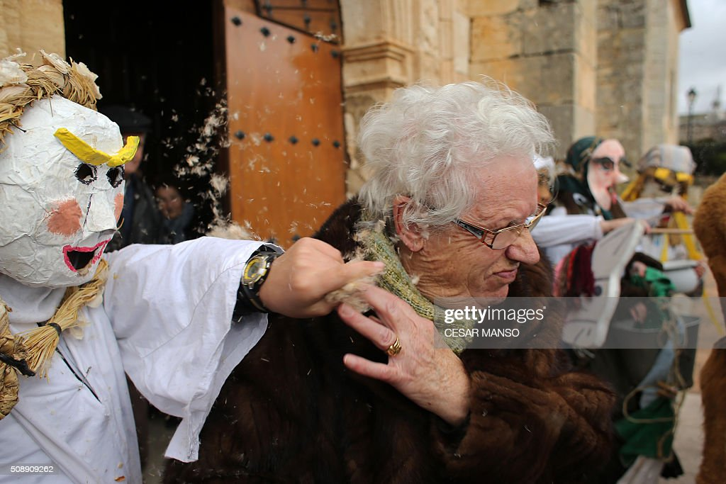 Participants throw feathers and resin as a women comes out the church during the celebration of 'El Gallo de Carnaval' (The Carnival's Cock) in Mecerreyes, in the northern Spanish province of Burgos, on February 7, 2016. The Gallo Carnival is a pagan festival in which people participate singing, dancing and attacking the 'Gallo' that is defended by Zarramacos. AFP PHOTO / CESAR MANSO / AFP / CESAR MANSO