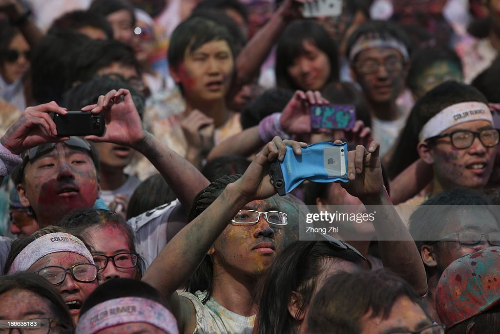 Participants use smart phones to take pictures in a Colour Run at the Guangzhou Olympic Center November 2, 2013 in Guangzhou, China. Thousands of people took part in the event.