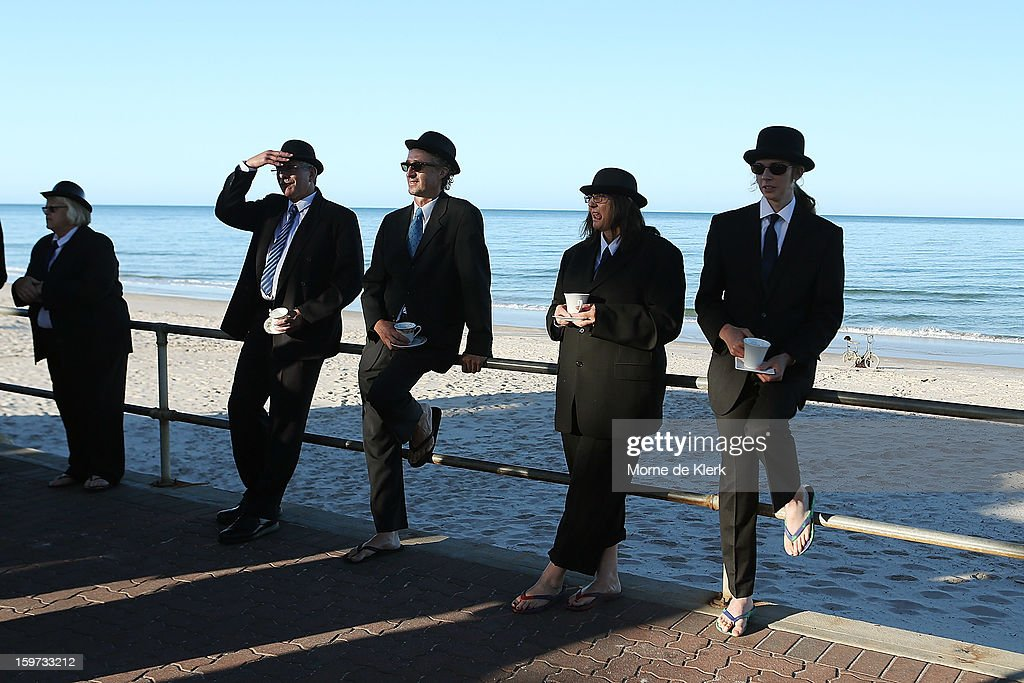 Participants wait before moving onto the beach dressed in suits and bowler hats as part of an art installation created by surrealist artist Andrew Baines on January 20, 2013 in Adelaide, Australia.