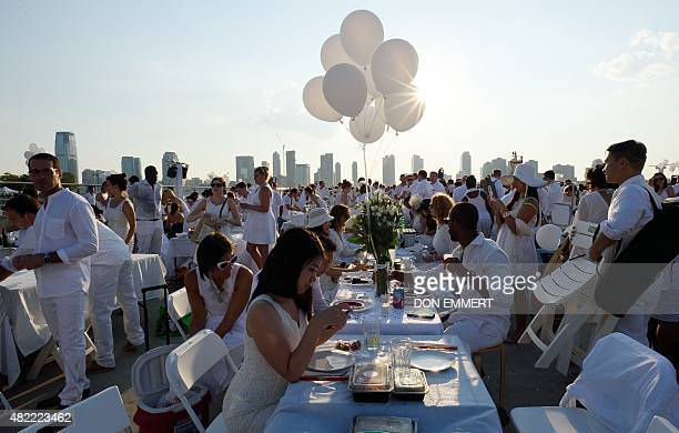 Participants wait for dinner at the annual Diner en Blanc at Pier 26 in New York on July 28 2015 An estimated 5000 people wore white and carried...