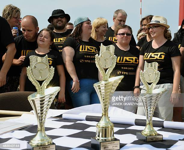 Participants wait for the award ceremony to start behind a table with trophies following the first TPG Deafblind Race on August 9 at the airport in...