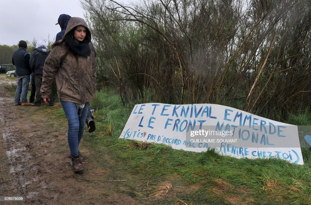 Participants walk by a sign reading 'Teknival against the Front national far-right party' during the 'Frenchtek 23Teknival' music festival near Salbris, central France on April 30, 2016. / AFP / GUILLAUME
