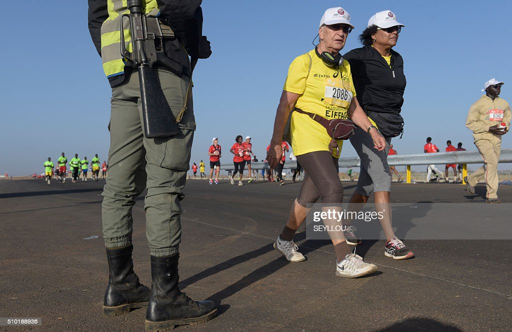Participants walk next to a gendarme in Dakar on February 14, 2016 during the first ever Dakar International Marathon long 42,195km in 2h 16mm 37s according to official results. The competition organised by the BTP Eiffage society started on February 13 in front of International Conference Center Abou Diouf (Cicad) on the outskirts of Dakar with different runs of 10 km and will end the day after, February 14, with a marathon. The BTP Eiffage society hosted the event to celebrates its 90 years of presence in Senegal. / AFP / SEYLLOU