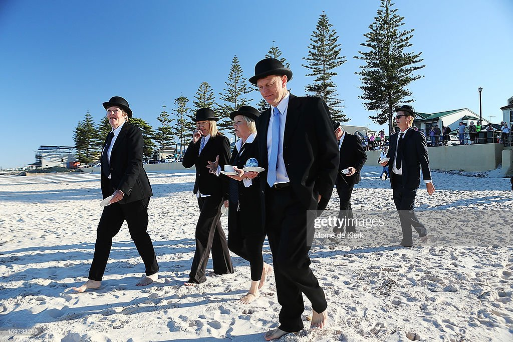 Participants walk onto the beach dressed in suits and bowler hats as part of an art installation created by surrealist artist Andrew Baines on January 20, 2013 in Adelaide, Australia.