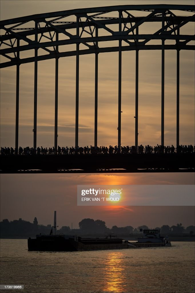 Participants walk over the Waal Bridge in Nijmegen on July 16 2013 at dawn on the first day of the International Four Day Marches of Nijmegen...