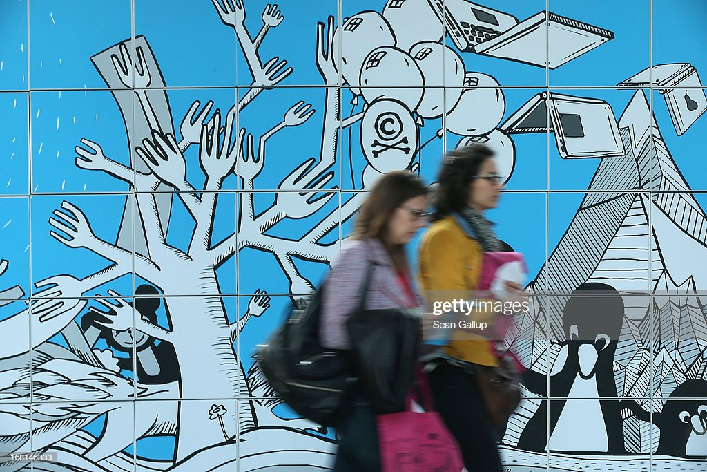 Participants walk past a decorated wall in between conferences on the first day of the re:publica 2013 conferences on May 6, 2013 in Berlin, Germany. Re:publica, a three-day-event, brings together bloggers and digitial media professionals for a series of conferences on affecting social, political and economic change through the Internet.