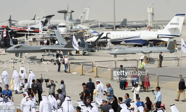 Participants walk past drones displayed during the Dubai Airshow on November 12 in the United Arab Emirates / AFP PHOTO / KARIM SAHIB