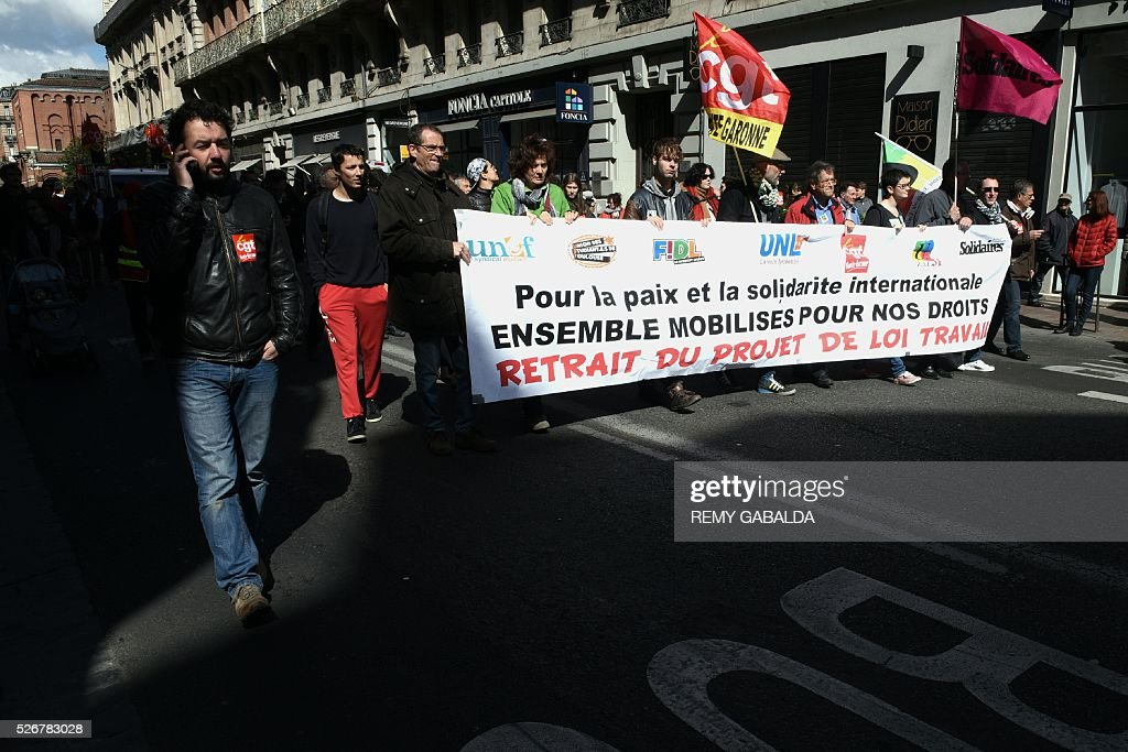 Participants walk with a banner as they protest against the government's proposed labour law reforms during the traditional May Day demonstration in Toulouse, southern France, on May 1, 2016. / AFP / REMY